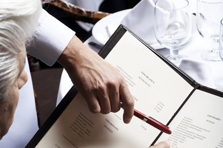 Senior businessman and waiter pointing at menu, view over shoulder